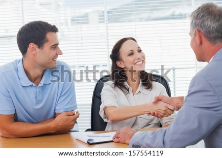 Pretty woman with her husband shaking hands with estate agent in bright office