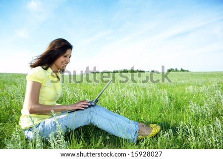 pretty woman with laptop on the green grass under blue sky