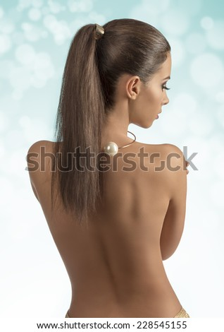 pretty woman with long brown hair-style ponytail showing her sexy naked back and wearing golden accessories