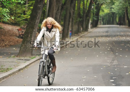 pretty woman with long curly golden hair riding a bike in park on autumn - stock photo