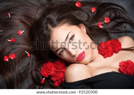 Pretty woman with long hair and red carnations - stock photo