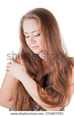 Pretty woman with long hair holding her shoulder, isolated on white - stock photo