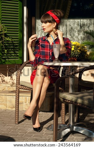 Pretty woman with long legs in red skirt, checked shirt, band, aviator sunglasses, patent leather shoes, resting in wickered chair in street cafe, drinking cold milk shake cocktail. On hot summer day - stock photo