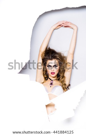 Pretty woman with long lush curly hair and sexy makeup on face in bra behind torn paper isolated on white background with raised hands