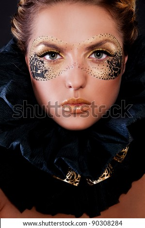 pretty woman with mask on face in gold - stock photo