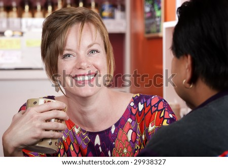 Pretty woman with red hair in coffee house with male friend - stock photo