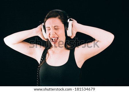 Pretty Woman With Retro Headphones Screaming. Pretty woman listening to loud music on retro headphones, singing or screaming. - stock photo