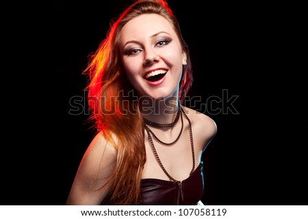 Pretty woman with smile looks at camera on black background - stock photo