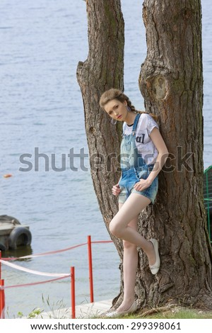 pretty woman with summer fashion casual clothes, denim overalls and t-shirt leaned on big tree near sea water, looking in camera  - stock photo