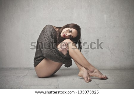 pretty woman with sweater sitting on the floor - stock photo