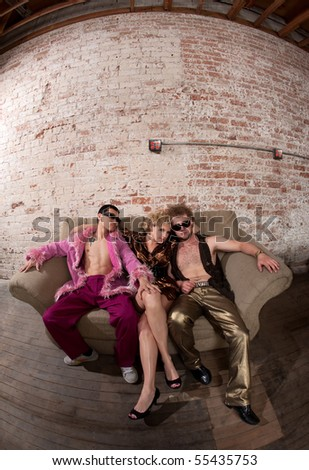 Pretty woman with two cool guys sitting on a sofa - stock photo