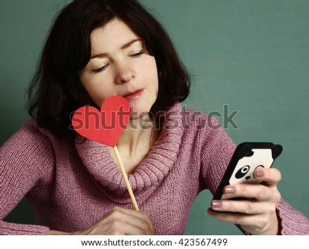 pretty woman with valentines day  red heart chatting with boyfriend online on smartphone close up portrait - stock photo