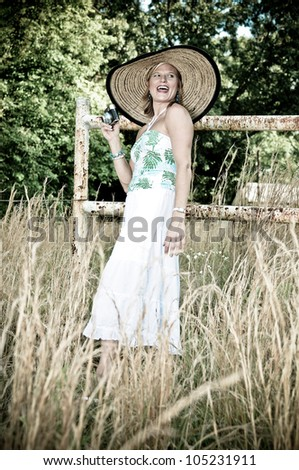 Pretty Woman with Vintage Camera in tall weeds and rusted fence. Photo in old color style. - stock photo