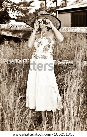 Pretty Woman with Vintage Camera in tall weeds and rusted fence. Photo in old sepia style. - stock photo