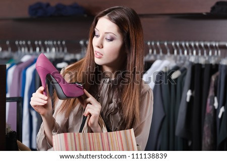 Pretty woman wonders at excellent fuchsia shoes - stock photo