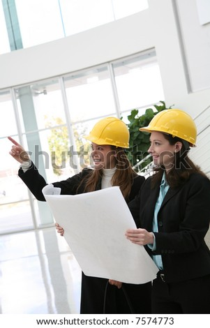 Pretty women architects inspecting the architecture at the work site - stock photo