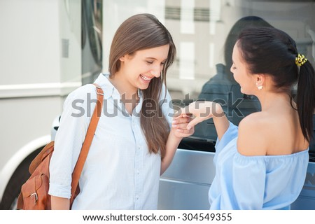 Pretty women are talking near a bus. One lady is showing to her friend her hand with ring boastfully. Another woman is looking at it happily and smiling - stock photo