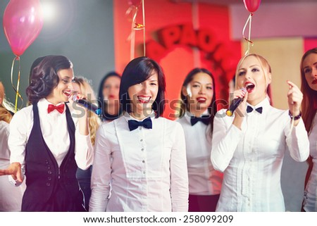 pretty women having fun on karaoke party - stock photo