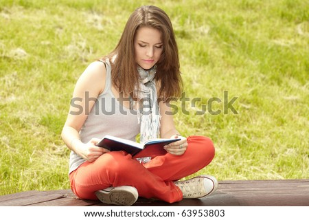 pretty women in the park with book