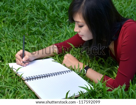 pretty women lying on green grass and writing book - stock photo