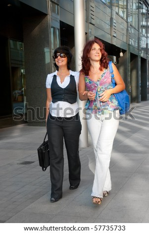 Pretty women walking down the street - stock photo
