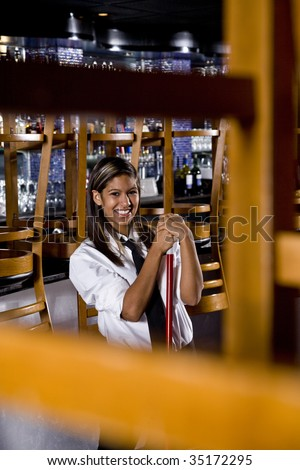 Pretty worker with a broom in a closed bar - stock photo