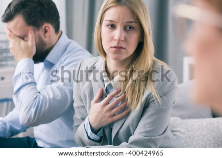 Pretty worried woman fighting about her destroyed marriage. In the background broken down husband - stock photo