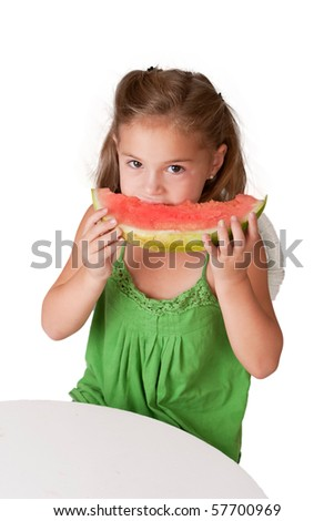 Pretty 5 year old girl eating watermelon at white table on a white background. - stock photo