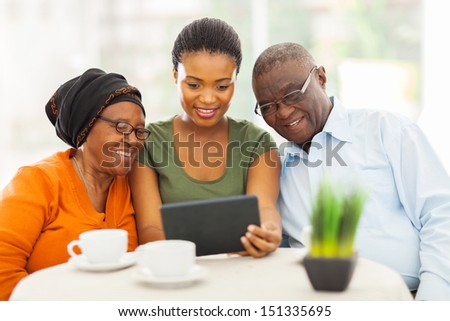pretty young adult african girl with senior parents using tablet computer - stock photo
