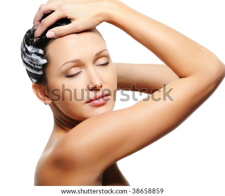 Pretty young adult woman washing her head with shampoo - stock photo