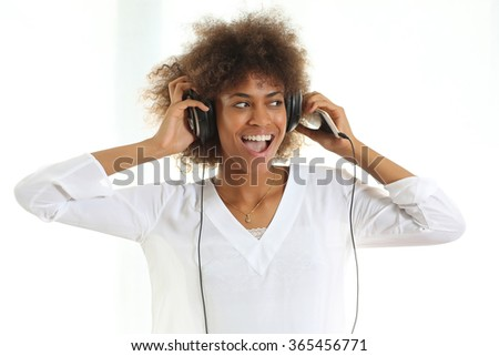 Pretty young african american girl listening music from her mobile phone her favorite singer. Standing against white background. - stock photo