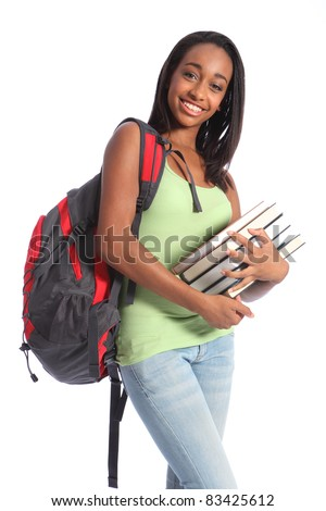 Pretty young African American teenager student girl with big smile wearing red backpack and holding school books. She has long black hair and wearing green vest and blue jeans. - stock photo