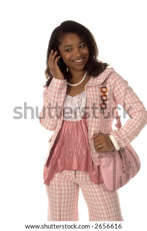 Pretty young African American woman dressed in a pink herringbone business suit talking on a cell phone and holding a leather purse