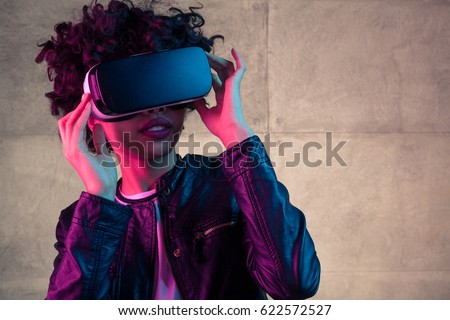 Pretty young African girl adjusting the VR headset on the white background