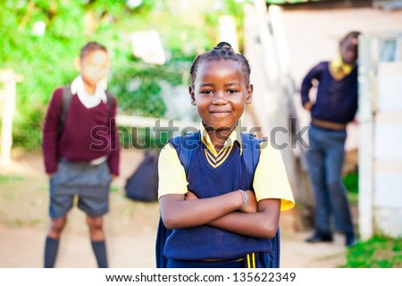 pretty young african girl standing proud in her yellow and blue school uniform with siblings watching over her. - stock photo