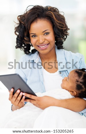 pretty young african mother holding tablet computer with baby at home - stock photo