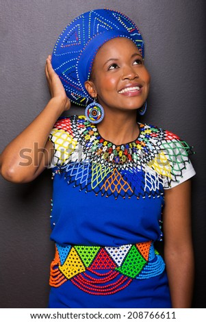pretty young african woman looking up on black background - stock photo