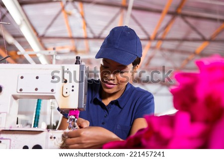 pretty young african worker sewing in clothing factory - stock photo