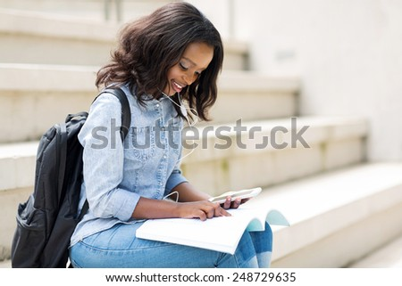 pretty young afro american college girl reading on campus - stock photo