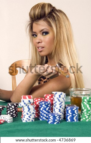 Pretty young Asian-American woman holds cigar  by stacks of poker chips and drink
