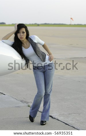 Pretty young Asian-American woman in blue jeans and white top stands leaning on nose cone of airplane on tarmac