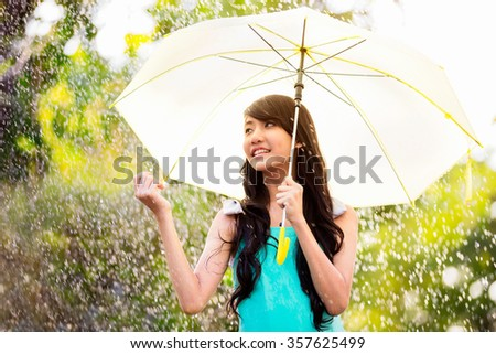 Pretty young asian girl in the rain - stock photo