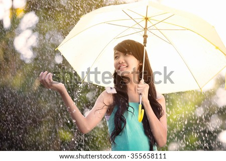 Pretty young asian girl in the rain with umbrella - stock photo