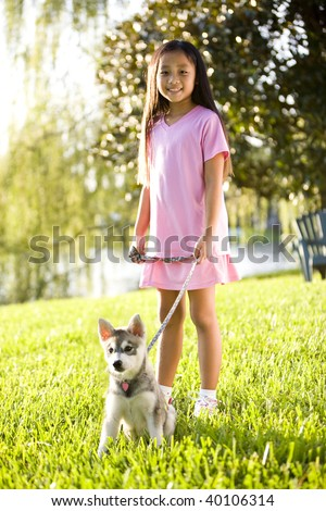 Pretty young Asian girl walking Alaskan Klee Kai puppy on leash on grass - stock photo
