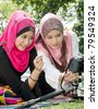 Pretty young Asian Muslim college girls discuss about photography - stock photo