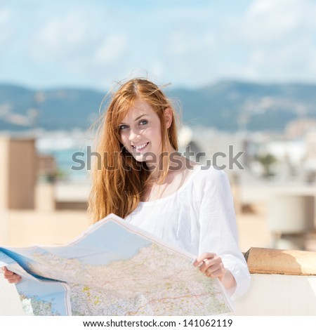 Pretty young au-pair studying a map while standing in the sun on a rooftop terrace - stock photo