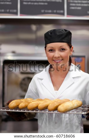 Pretty young baker with baguettes in the kitchen - stock photo