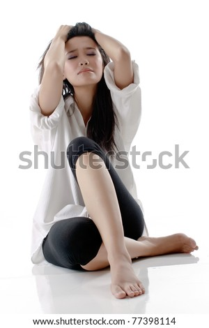 Pretty young beautiful Asian woman with depression looks against isolated white background - stock photo
