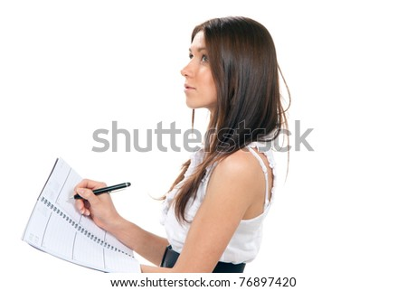 Pretty young beautiful woman standing, writing, take notes, holding textbook notebook organizer in hand and pen in another thinking on a white background - stock photo