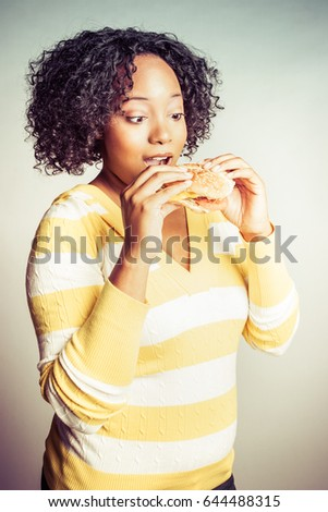 Pretty young black woman eating sandwich